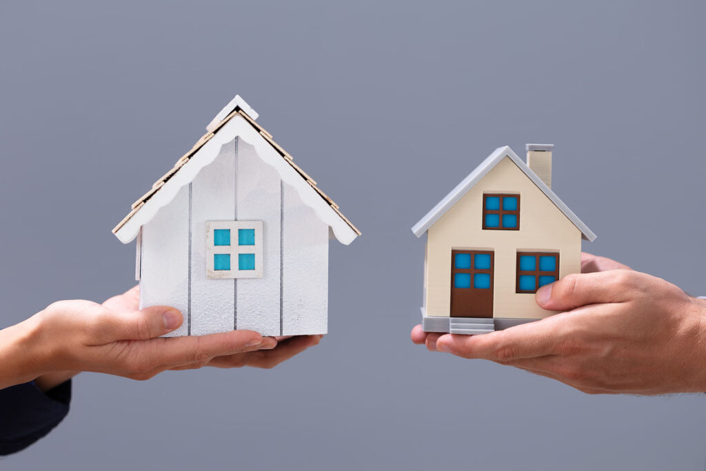 Hands of two people holding model homes in their hands preparing to exchange properties
